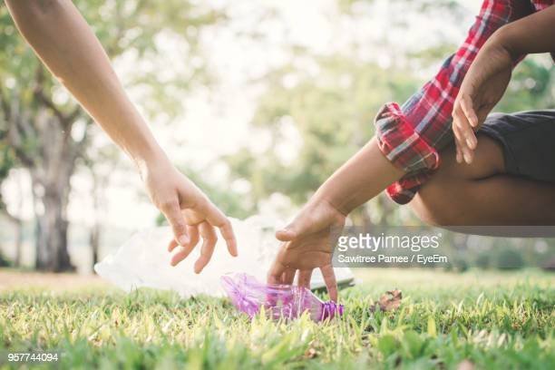 Cropped Hands Picking Plastic Water Bottle From Grassy Field At Public Park