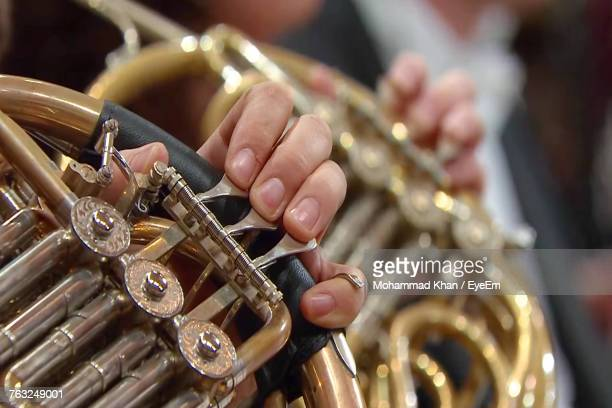 Cropped Hands Playing Brass Instruments