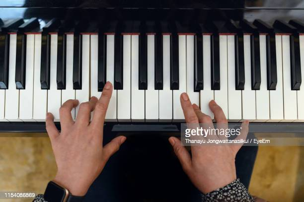 cropped hands playing piano - piano key stock pictures, royalty-free photos & images