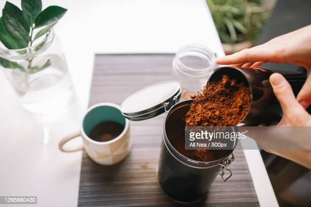 cropped hands pouring ground coffee into reusable container, lleida, spain - images stock pictures, royalty-free photos & images