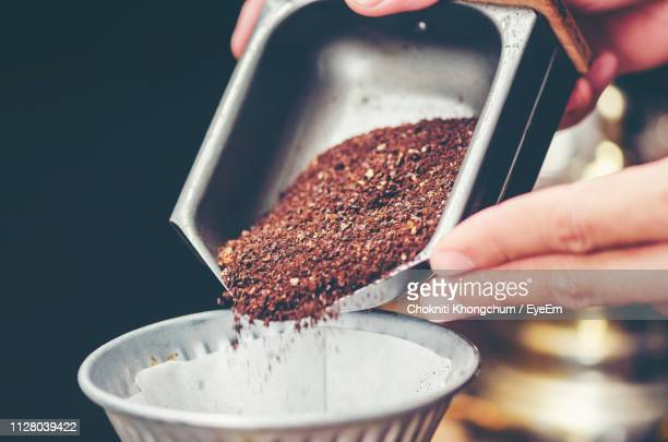 cropped hands pouring grounded coffee in filter - ground coffee stock photos and pictures