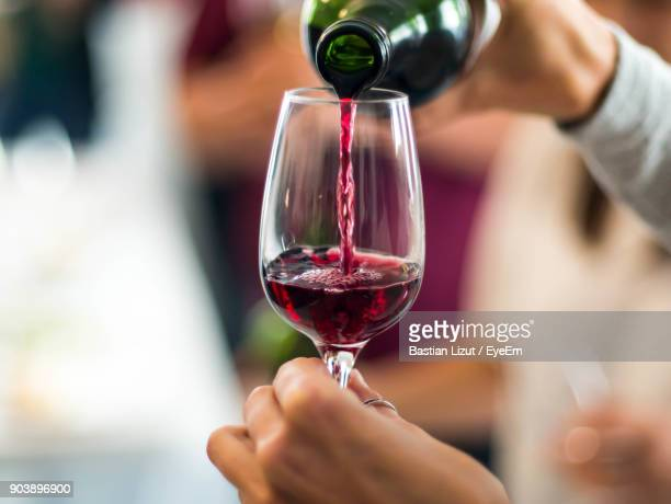 Cropped Hands Pouring Red Wine In Wineglass