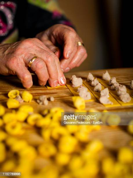 cropped hands preparing food at table - emilia romagna stock pictures, royalty-free photos & images