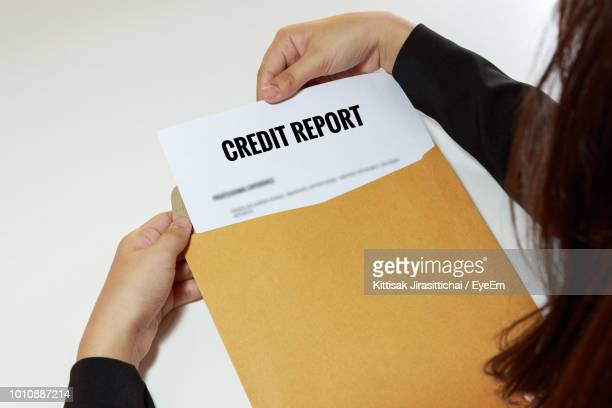 Cropped Hands Removing Credit Report From Envelope At Table