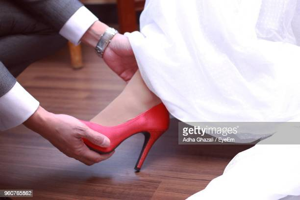 Cropped Hands Removing High Heels Of Bride