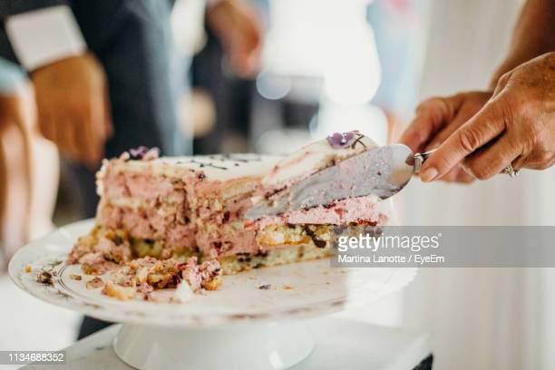 cropped hands serving cake in plate at wedding ceremony - serving food and drinks stock pictures, royalty-free photos & images