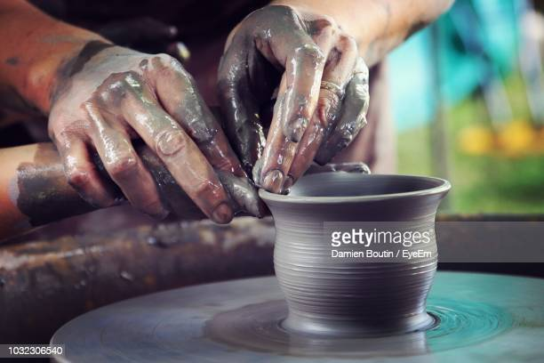 cropped hands shaping clay on pottery wheel - lehm mineral stock-fotos und bilder