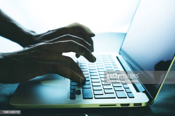 Cropped Hands Using Laptop