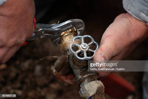 Cropped Hands Using Pliers On Pipe At Field