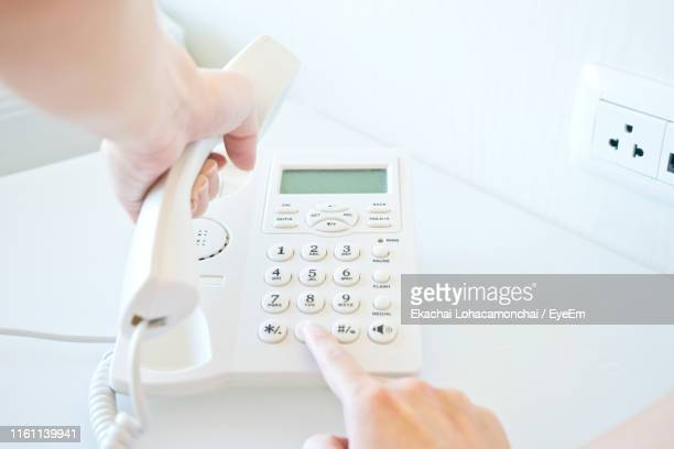 cropped hands using telephone at table - landline phone stock pictures, royalty-free photos & images