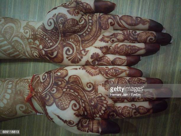 Cropped Hands With Henna Tattoo On Table