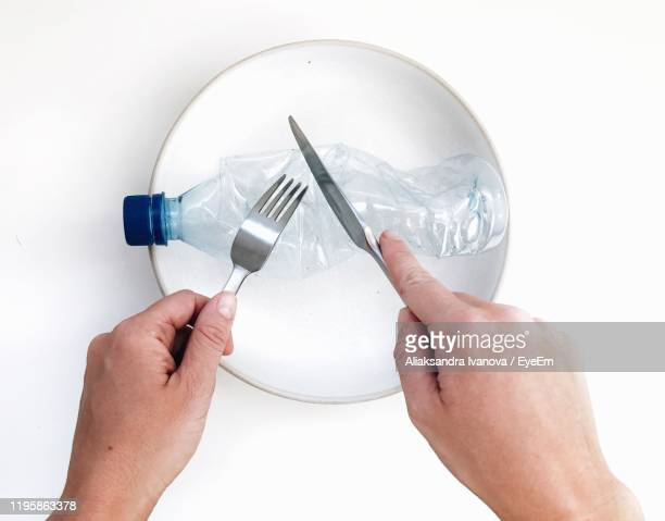 cropped hands with plastic bottle in plate - plastic plate stock pictures, royalty-free photos & images