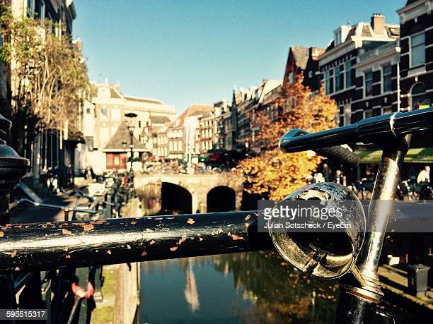 Cropped Image Of Abandoned Bicycle By Canal In City
