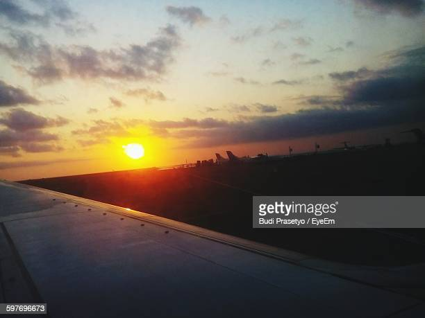 Cropped Image Of Aircraft Wing At Airport Runway Against Sunset Sky