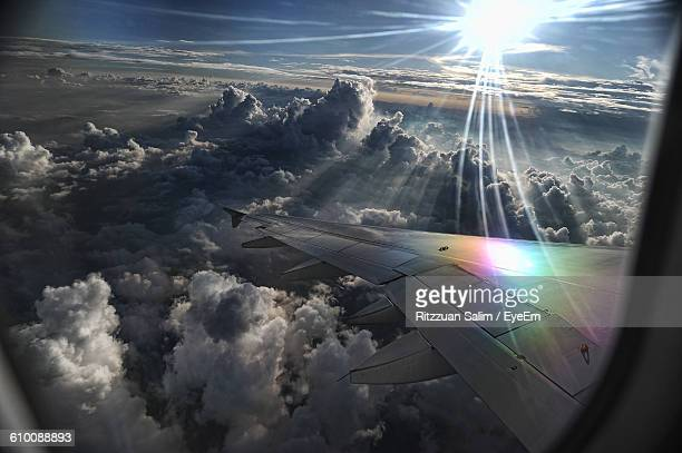 Cropped Image Of Aircraft Wing Over Clouds Seen Through Window
