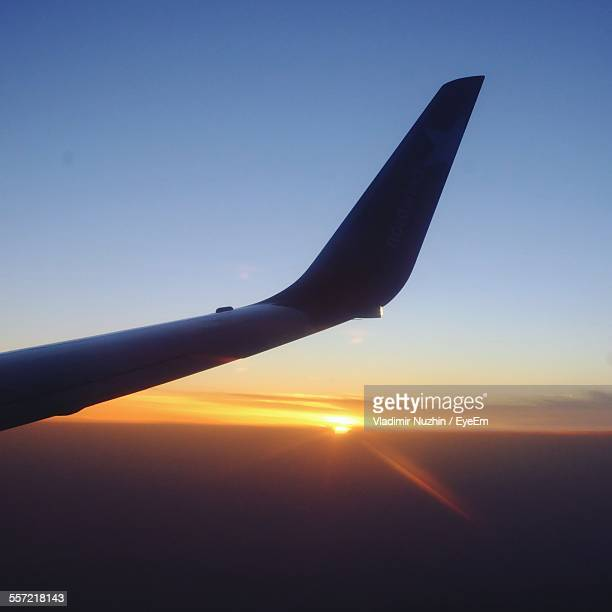 cropped image of airplane during sunset - airplane tail stock pictures, royalty-free photos & images
