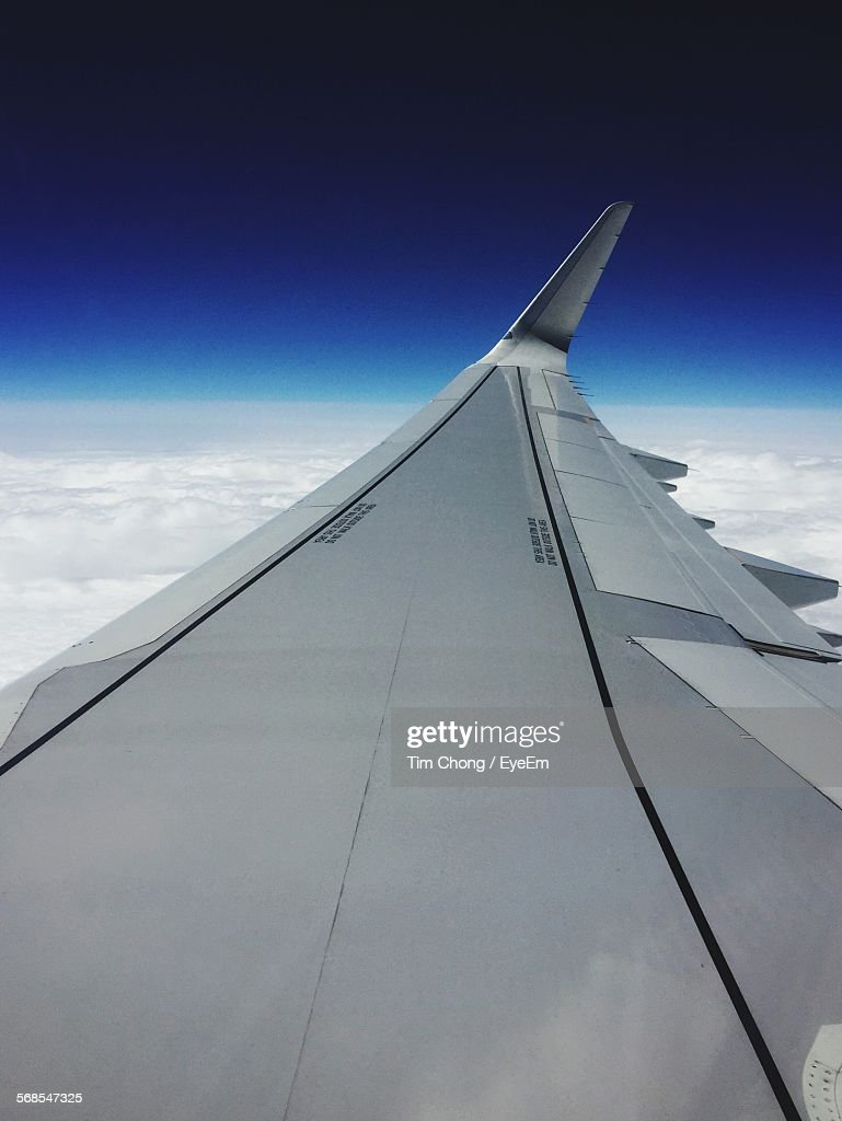 Cropped Image Of Airplane Flying Above Clouds In Sky : Stock Photo