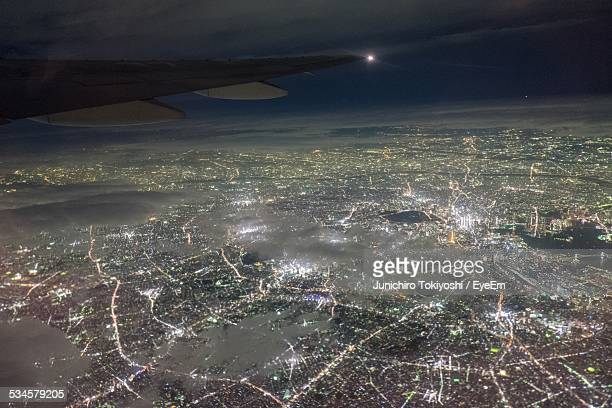 cropped image of airplane flying above illuminated city at night - 関東地方 ストックフォトと画像