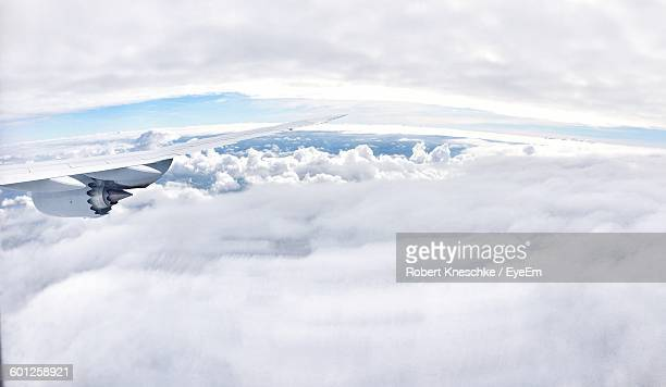 Cropped Image Of Airplane Flying Against Cloudy Sky