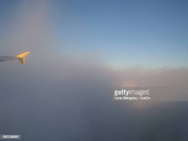cropped image of airplane flying in cloudy sky - flugzeugheck stock-fotos und bilder