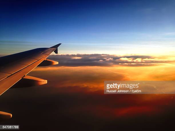 Cropped Image Of Airplane Flying In Sky During Sunset