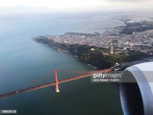 Cropped Image Of Airplane Flying Over 25 De Abril Bridge