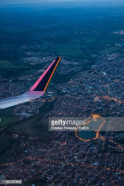 cropped image of airplane flying over cityscape at dusk - belo horizonte stock pictures, royalty-free photos & images