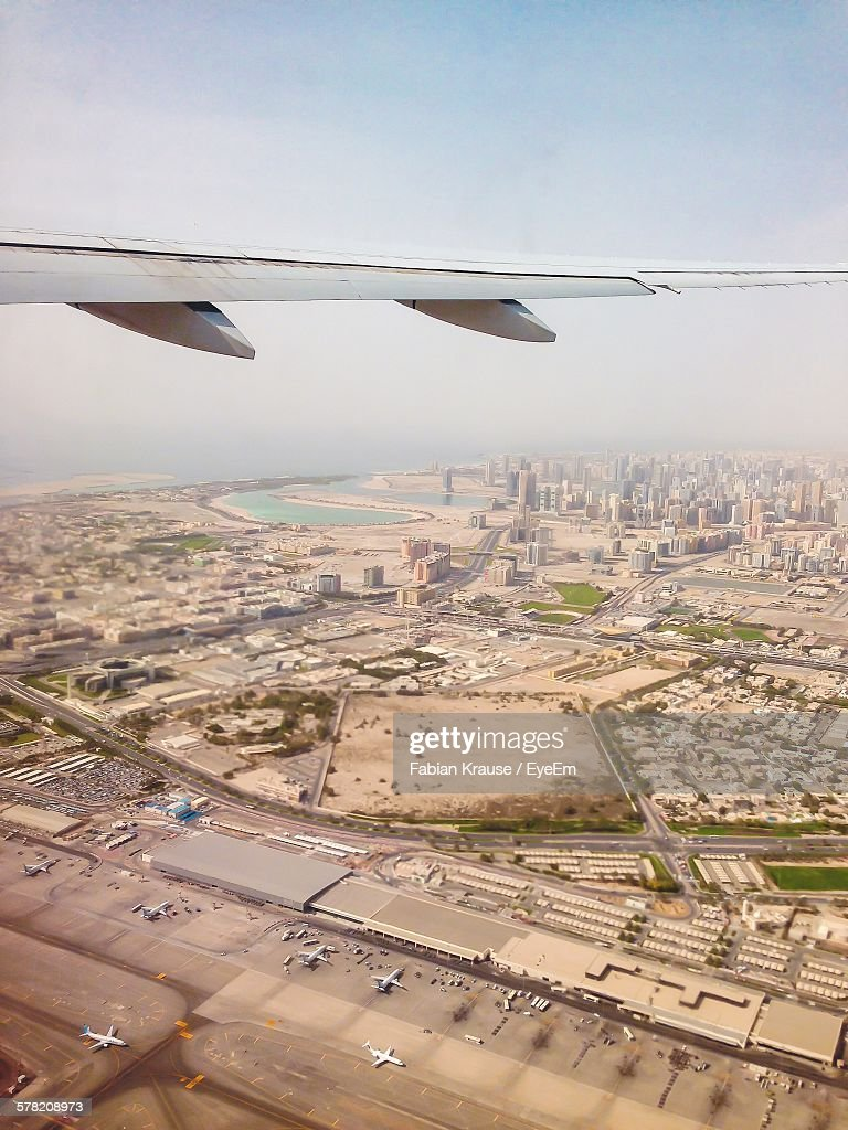 Cropped Image Of Airplane Flying Over Cityscape : Stock Photo