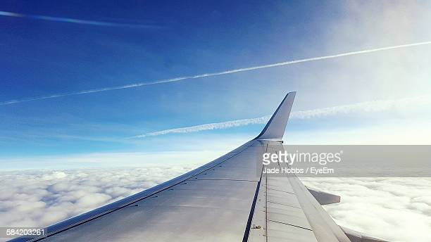 cropped image of airplane flying over clouds - aircraft wing stock pictures, royalty-free photos & images