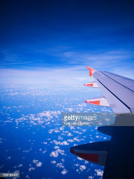 cropped image of airplane flying over clouds - lyra stock photos and pictures