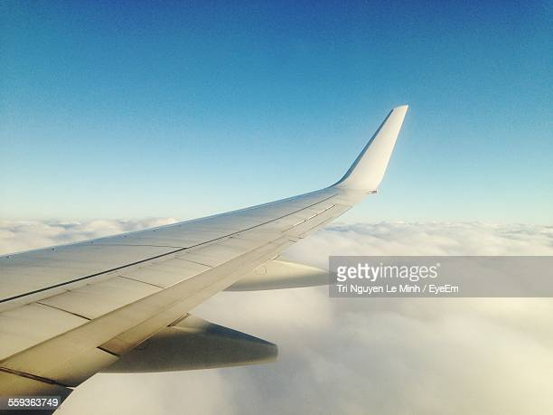 Cropped Image Of Airplane Flying Over Cloudscape Against Clear Blue Sky