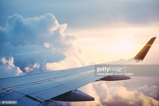 cropped image of airplane flying over cloudy sky - aircraft wing stock pictures, royalty-free photos & images