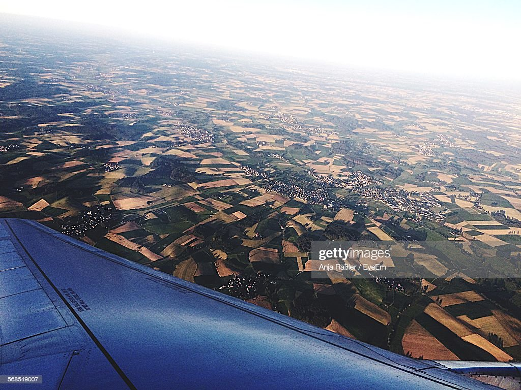 Cropped Image Of Airplane Flying Over Field : Stock Photo