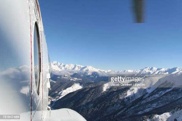 Cropped Image Of Airplane Flying Over Snowcapped Mountains Against Blue Sky