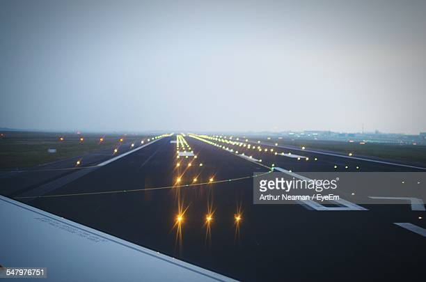 Cropped Image Of Airplane On Illuminated Airport Runway At Berlin Schonefeld Airport