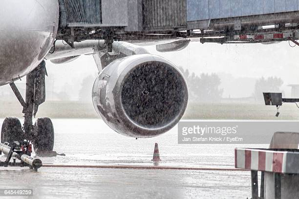 Cropped Image Of Airplane On Runway During Rainfall