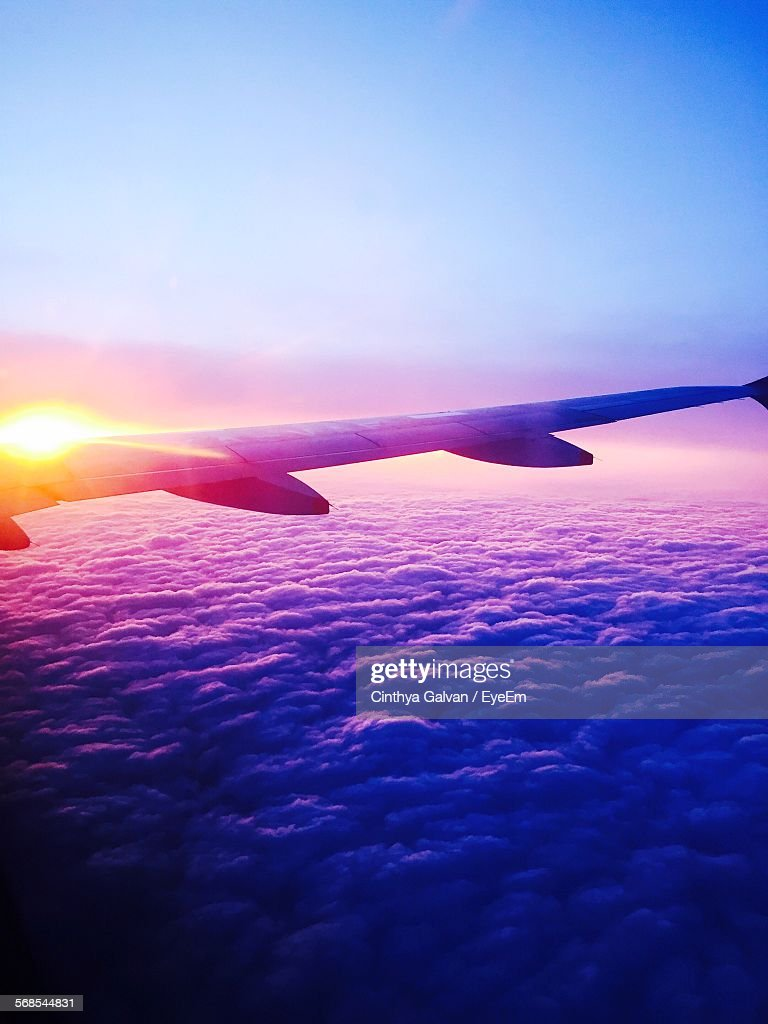 Cropped Image Of Airplane Over Clouds Against Sky During Sunset : Stock Photo