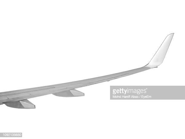 cropped image of airplane wing against white background - aircraft wing stock pictures, royalty-free photos & images
