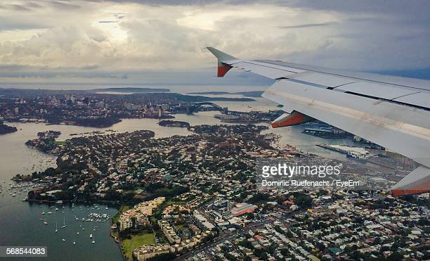 Cropped Image Of Airplane Wing Flying Over City And Harbor In Cloudy Sky