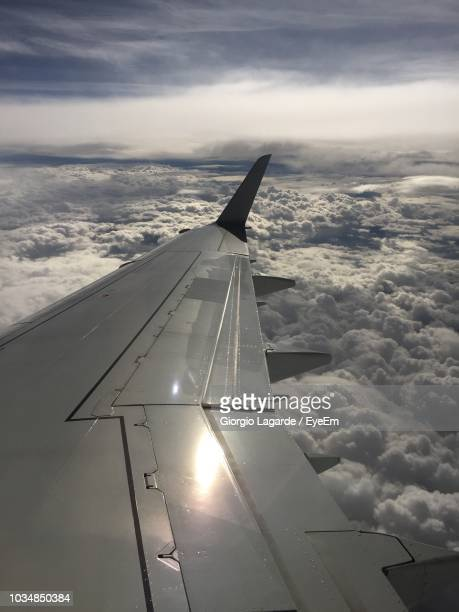cropped image of airplane wing flying over cloudscape - lagarde stock photos and pictures