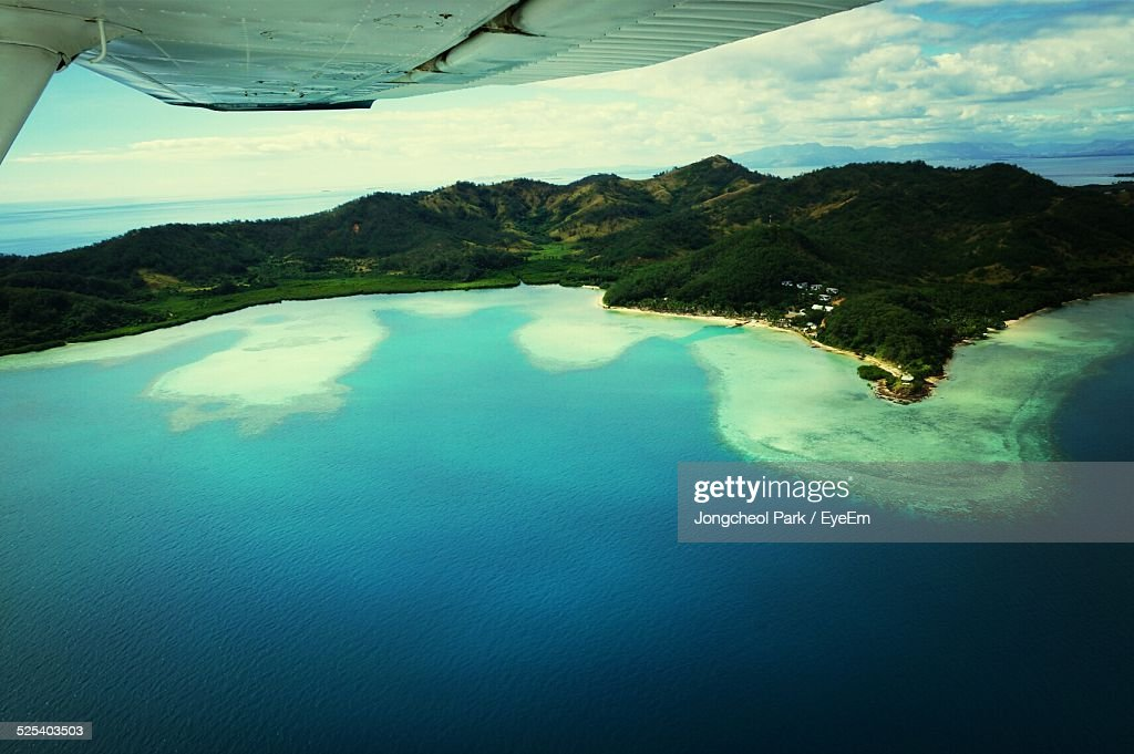 Cropped Image Of Airplane Wing Over Sea : Stock Photo
