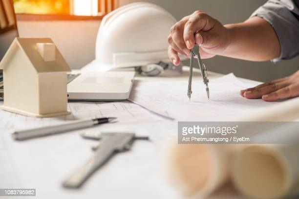 cropped image of architect making blueprint in office - drawing compass stock pictures, royalty-free photos & images