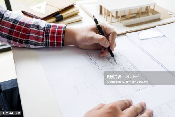 cropped image of architect making blueprint in office - printed sleeve stock pictures, royalty-free photos & images