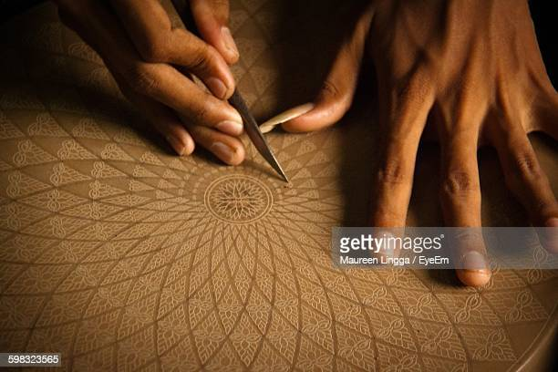 cropped image of artist carving on wood - craftsman stock photos and pictures