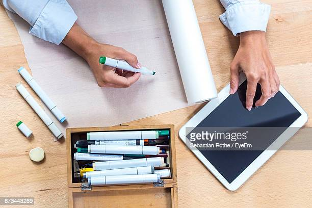 Cropped Image Of Artist Drawing On Paper While Using Digital Tablet On Table