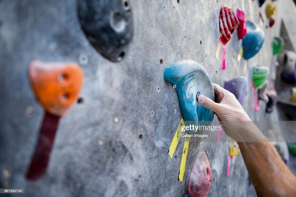 Cropped image of athlete holding rock on climbing wall : Stock Photo
