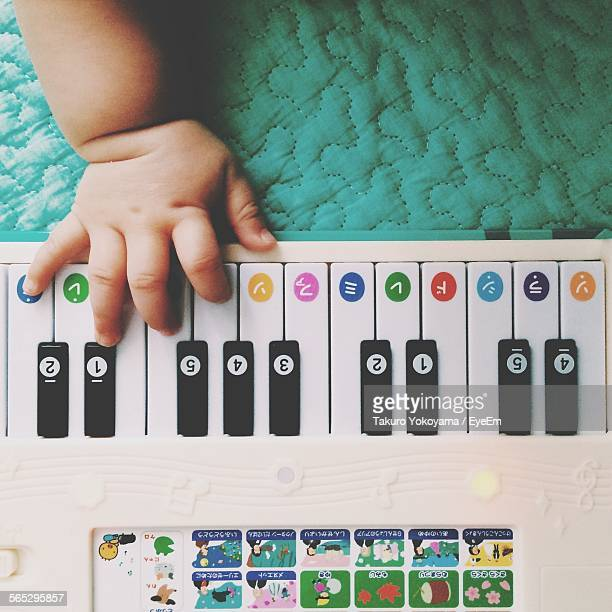 Cropped Image Of Baby Hand Playing With Toy Piano