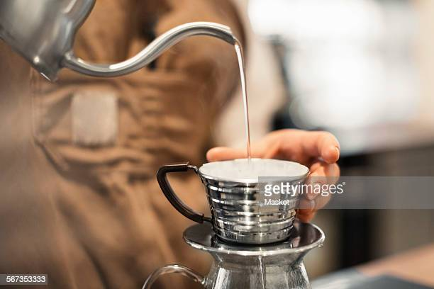 Cropped image of barista pouring water in coffee cup at cafe