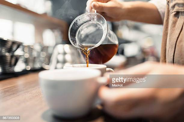 Cropped image of barista preparing coffee at counter