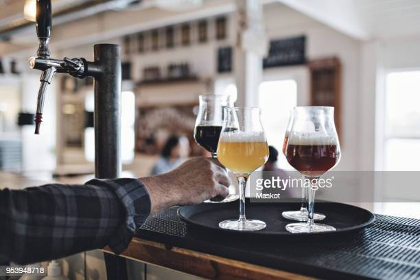Cropped image of bartender keeping beer glass on tray at counter